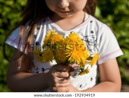 Girl with a bouquet of yellow dandelions