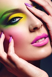 Girl with a bright make-up. A portrait of a beautiful young girl with make-up in bright colors - green and yellow shadows, pink lipstick. Manicure - lilac nails. Blonde. Fashion, beauty, beauty salon.