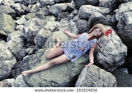 Girl with a broken and a broken head is on the rocks