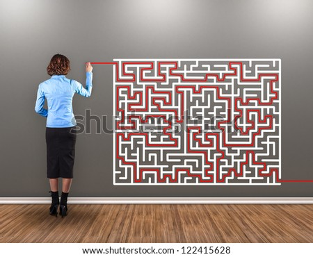 Girl with a brush in a hand draws a way from a labyrinth