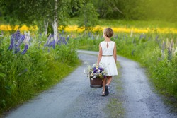 Girl with a bucket of flowers walking on a dirt road