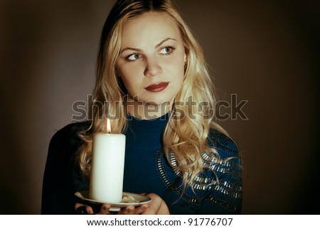 Girl with a candle in a dark room