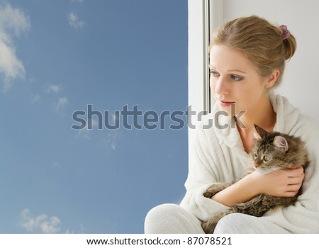girl with a cat looking out the window
