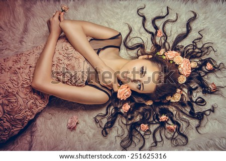 girl with a circlet of flowers on head. charming girl with a flowers. young woman has a beautiful face. girl lying on fur with her long hair