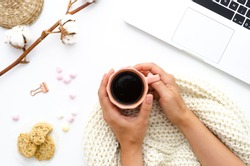 girl with a coffee in her hands. Oatmeal cookies, laptop, and sweets. A good start to a winter day. Cotton flowers decorate the table. Autumn or Winter concept. Flat lay, top view