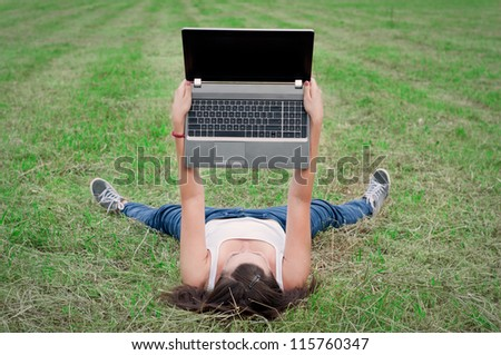 girl with a computer lying on the grass