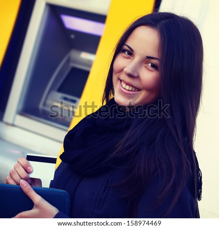 girl with a credit card at an ATM