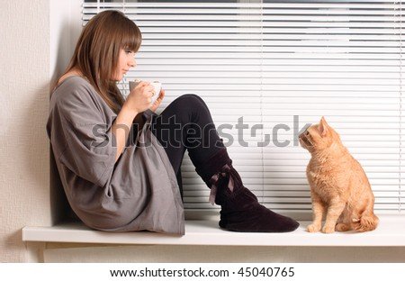 Girl with a cup of cappuccino and a cat at the window