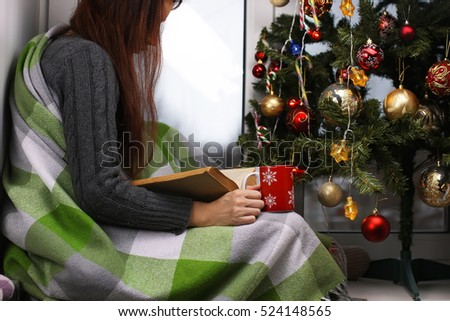 Girl with a cup of hot drink stands in front of a window in the New Year's Eve