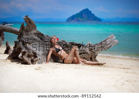 girl with a flower on the beach - stock photo
