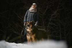 girl with a German shepherd walking on a winter night in the Park. Photo on the background of a dark forest.