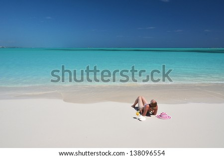 Girl with a glass of orange juice on the beach of Exuma, Bahamas