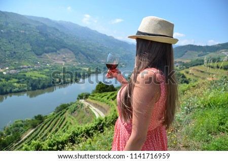 Girl with a glass of wine looking to the vineyards in Douro Valley, Portugal #1141716959