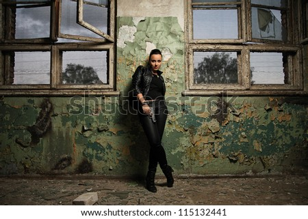 girl with a gun standing against the wall