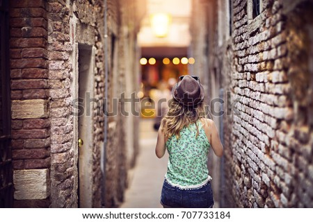 Girl with a hat walking and discovering places in narrow street. #707733184