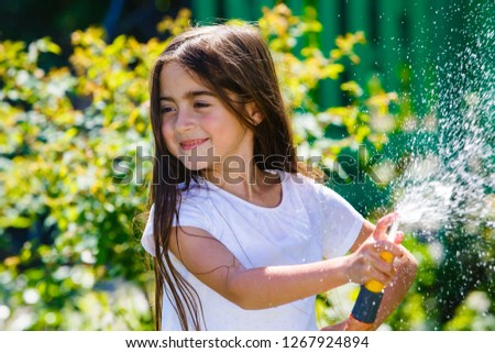 girl with a hose sprays water at the dacha.