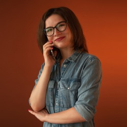 Girl with a mobile phone. Beautiful smile. Dimple. broad smile. Blue denim dress with buttons and pockets. Brown background. One person. Communication by phone. Joy. Positive. funny