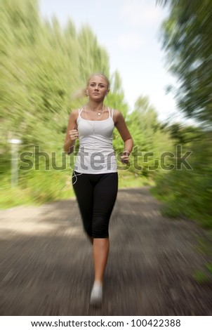 Girl with a music player running on the road