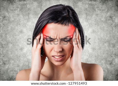 Girl with a painful head on a grey background