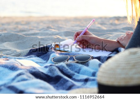 girl with a paper notebook by the sea works. freelancing  #1116952664