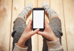 Girl with a phone in her hands sitting on the wooden floor.top view