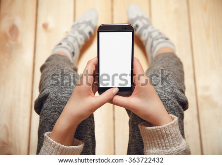 Girl with a phone in her hands sitting on the wooden floor.\top view