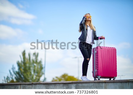 girl with a pink suitcase on a...
