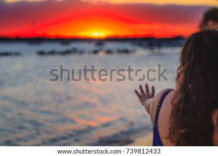 Girl with a ring in her hand symbolizing marriage. Sunset in the background, ring in focus with blurred background.