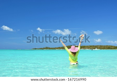 Girl with a seashell in the turqouise water of Atlantic. Exuma, Bahamas