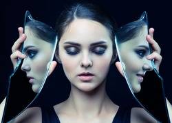 Girl with a shard of the mirror. Female with mirror shard in hand posing on gray background. Face reflection in mirror splinter. Eyes closed.