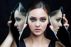 Girl with a shard of the mirror. Female with mirror shard in hand posing on gray background. Face reflection in mirror splinter.