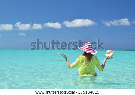 Girl with a shell in her hand in the turquoise Atlantic water. Exuma, Bahamas