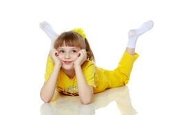 Girl with a short bangs on her head and bright yellow overalls.She crouched down on the white advertising banner.