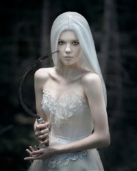 Girl with a sickle in her hand in a white wig and a wedding dress