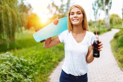 Girl with a skate in the Park, drinking a drink with a glass bottle, summer mood