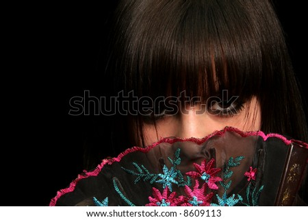 Girl with a spanish fan, on black background