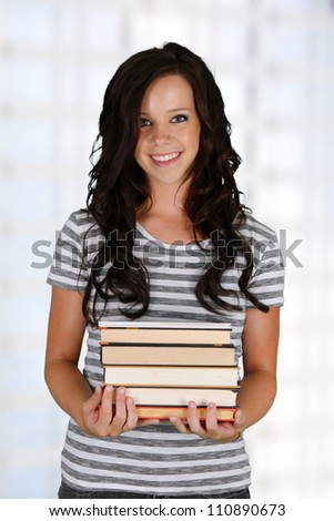 Girl with a stack of books at her school