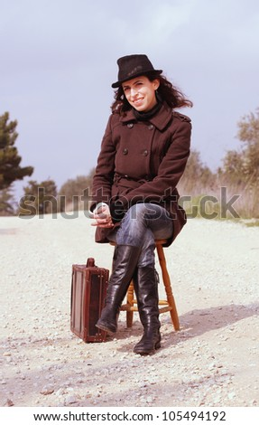 Girl with a suitcase sitting on a stool
