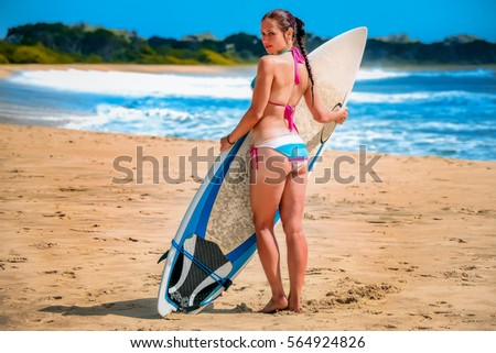 Stock Photo Girl with a surf board on the beach