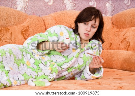 girl with a thermometer and a nasal spray on the couch