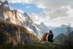 girl with a toller dog in the mountains. Autumn mood. Traveling with a pet. Nova Scotia Duck Tolling Retriever