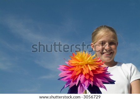 girl with a vibrant paper flower at the beach (blue sky, copy space)