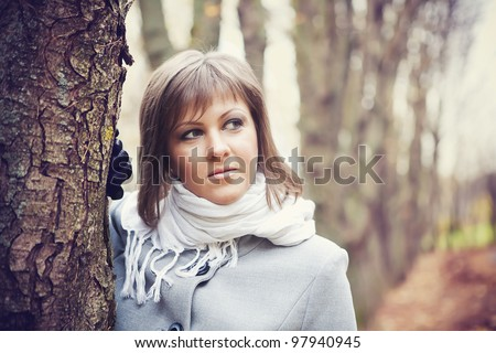 Girl with a white scarf looks into the distance