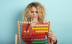 Girl with abacus is confused about the sum . cyan background