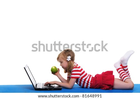 girl with an apple and laptop lying on blue rug