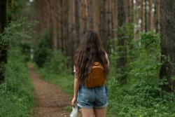 girl with an orange backpack behind her back walking on a forest path. Girl in the pink t-shirt and denim shorts walking in the woods.