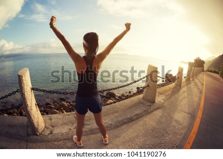 Girl with arms outstretched at a seaside. Beautiful inspiring landscape and sea with girl and hands raised on sunrise