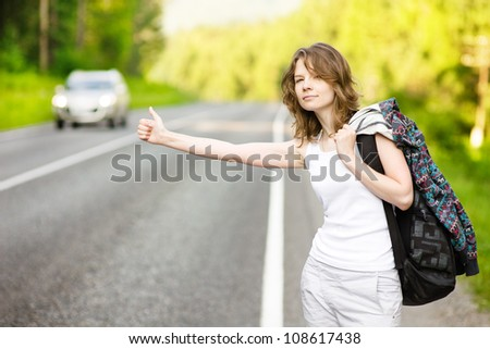 girl with backpack stops the car on road