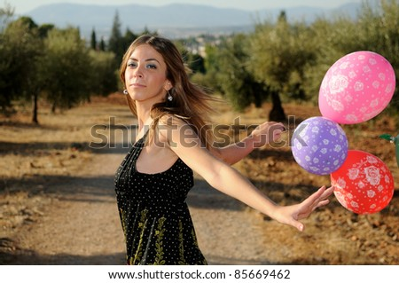 Girl with balloons in the field