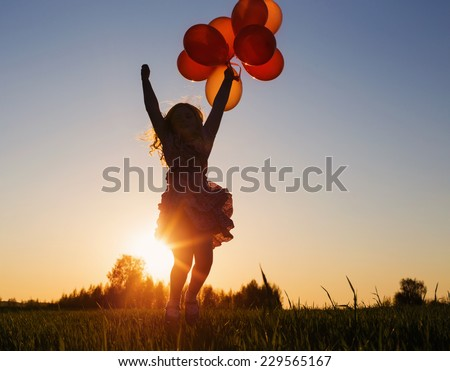 Stock Photo girl with balloons jumping outdoor